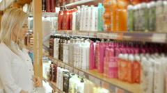 Beautiful Woman Choosing Body Care Products In Supermarket Stock Footage