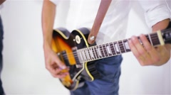 Man playing guitar in the studio on a white background, close-up - stock footage
