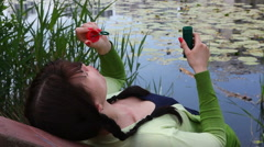 Young woman makes bubble blower in city park, near lake and reeds Stock Footage