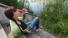 Beautiful girl makes bubble blower in city park, near lake and reeds Stock Footage