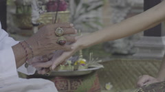 Balinese priest holding women's hand doing palm reading, ungraded Stock Footage