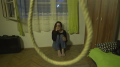 Desperate and beaten girl sits on floor,fly cam shot through the rope on ceiling Stock Footage