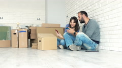 Young couple with smartphones talking about new home project on floor Stock Footage