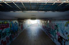 Pedestrian underpass tunnel with painted of graffiti on the walls - stock photo