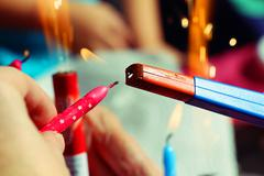 Someone holding pink birthday candle in the hand and light it with a lighter Stock Photos