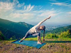 Woman practices yoga asana Utthita Parsvakonasana outdoors - stock photo