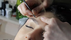Beautician draws eyebrows - stock footage
