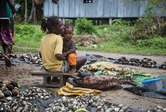 Seghe, Solomon Islands - June 16, 2015: Girl selling mussels and holding baby on Stock Photos