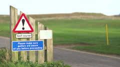 Walkers crossing a golf course with warning sign - half speed Stock Footage