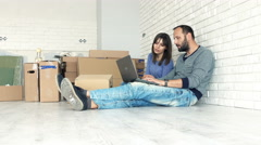 Young couple with tablet and laptop talking about new home project on floor Stock Footage