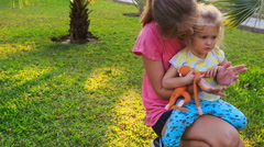 Blond Mother Daughter Squat on Grass among Palms in Park - stock footage