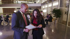 4K Businessman and businesswoman in discussion in modern corporate building - stock footage