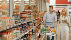 Customers Shopping In Supermarket And Checking List Of Products On Tablet PC Stock Footage