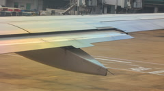 Passenger Loading Bridge behind Airliner Wing on Airfield Stock Footage