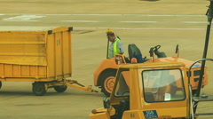Airport Worker Clings Bulk Cargo Loader to Truck on Airfield - stock footage