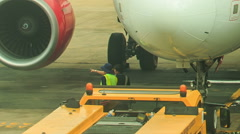 Airport Workers Talk under Engine by Fuselage on Airfield - stock footage