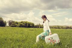 Smiling happily girl with vintage suitcase - stock photo