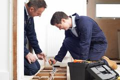 Plumber And Apprentice Fitting Central Heating In House - stock photo