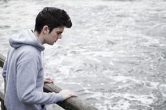 Depressed Young Man Contemplating Suicide On Bridge Over River Stock Photos