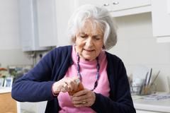 Senior Woman Struggling To Take Lid Off Jar Stock Photos