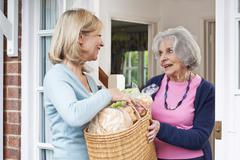 Female Neighbor Helping Senior Woman With Shopping Stock Photos