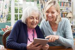 Female Neighbor Showing Senior Woman How To Use Digital Tablet Stock Photos