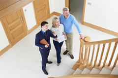 Realtor Showing Mature Couple Around House For Sale Stock Photos