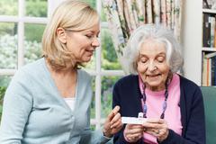 Female Neighbor Helping Senior Woman With Medication Stock Photos