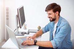 Contented man using his laptop Stock Photos