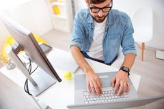 Guy tapping on his laptop Stock Photos