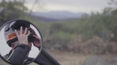 Biker reflecting in mirror by wearing motorcycle helmet Stock Footage