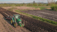 Aerial: Farmer Plowing a Field on a Sunny Day Stock Footage