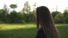 Teen girl walking in park in sunset from behind shot with stabilizer Stock Footage