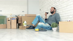 Young man drinking red wine sitting on floor at his new home Stock Footage