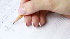 Hand with pencil and music sheet. composer writes music - stock footage