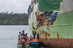 Seghe, Solomon Islands - June 16, 2015: Ship anchored at Seghe harbor with peopl - stock photo