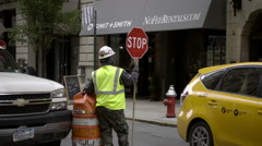construction worker holding stop sign and taxi cab driving down street in NYC - stock footage