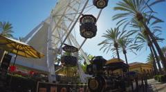 Low Angle Spinning Ferris Wheel Sun Shining Through Cars Stock Footage