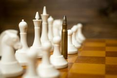 Conceptual photo of bullet in row of pawns. Concept of military conflict Kuvituskuvat