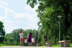 Happy family of four people walking in park the city Stock Photos