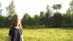 Teen girl walking in park in sunset to camera shot with stabilizer Stock Footage