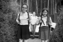 Black and white portrait of cheerful girls going to school at morning - stock photo