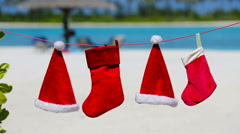 Red Santa hats and Christmas stocking hanging on tropical beach Stock Footage