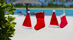 Red Santa hats and Christmas stocking hanging on tropical beach - stock footage