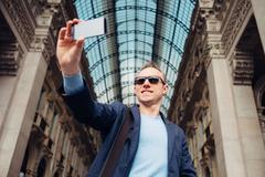 Tourist man take his photo in Galleria Vittorio Emanuele in Milan - stock photo