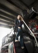 Beautiful young woman posing on big black steam locomotive - stock photo