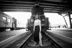 Black and white photo of woman posing on rails in front of retro train - stock photo