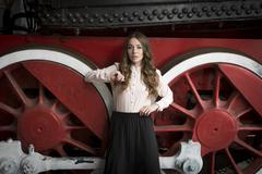 Portrait of beautiful woman leaning on big red wheel of old train Stock Photos