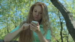 Young red-haired girl in the apple orchard looking at the phone Stock Footage