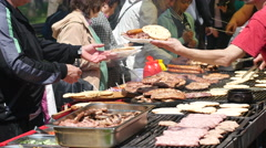 People buy meat dishes grilled on big street food festival in Sofia meat eating Stock Footage